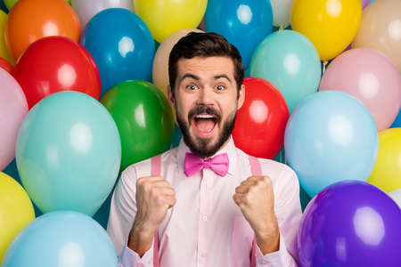 Photo of funny handsome guy colorful decorations ready birthday party festive mood raise fists meet guests wear pink shirt bow tie suspenders on balloons creative design background Stok Fotoğraf