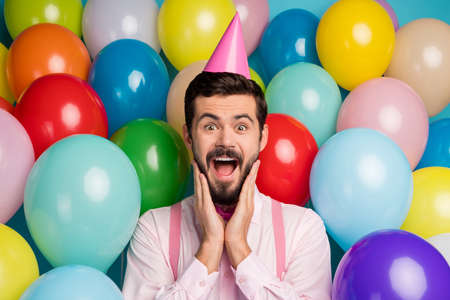 Photo of funny gentleman guy colorful balloons everywhere arrange birthday party not believe eyes wear paper cone cap pink shirt bow tie suspenders on balloons creative background Imagens