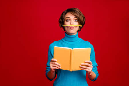 Portrait of funny crazy girl hipster have rest relax during writing report hold copy book pencil nose fooling feel carefree wear blue jumper isolated red bright color background Stock Photo