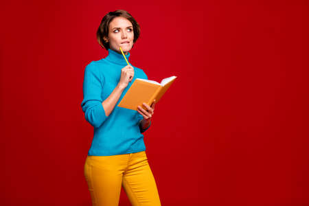 Portrait of intelligent girl write report hold copybook think thoughts difficult questions bite lips look shine copyspace wear blue jumper yellow pants trousers isolated red color background