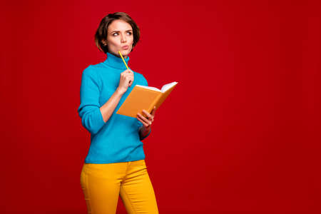 Portrait of clever concentrated girl prepare for lecture make project think thoughts hold copy book touch pencil cheek look copyspace wear blue yellow jumper isolated red color background