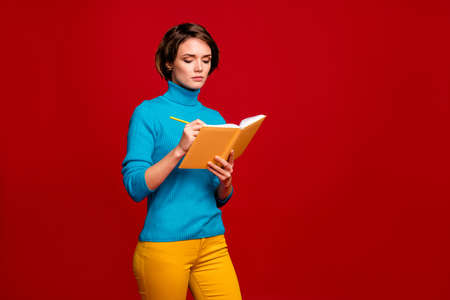 Portrait of focused clever girl write notes in her copybook make report for college courses lectures wear casual style clothing isolated over red color background