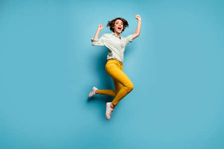 Full size photo of funky lady jumping high up celebrating weekend vacation start beginning wear casual green shirt yellow pants shoes isolated blue color background Stock fotó