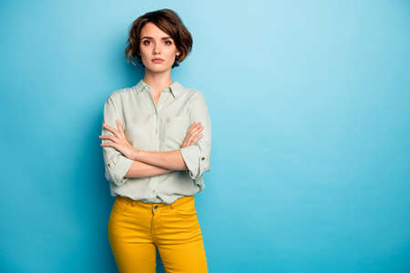 Photo of nice attractive business lady short hairstyle not smiling serious responsible person arms crossed wear casual green shirt yellow pants isolated blue color background