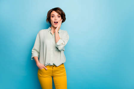 Photo of funny beautiful lady short hairdo look open mouth read discount banner advert arm on chin wear casual green shirt yellow trousers isolated blue color background Stock fotó