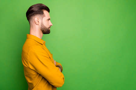 Profile photo of handsome young business man crossed arms watch colleagues work responsible boos serious person formalwear yellow shirt isolated green color background