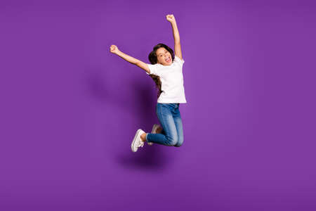 Full length body size view of her she nice attractive cheerful wavy-haired girl jumping having fun rising hands up isolated on bright vivid shine vibrant purple violet lilac color background Standard-Bild
