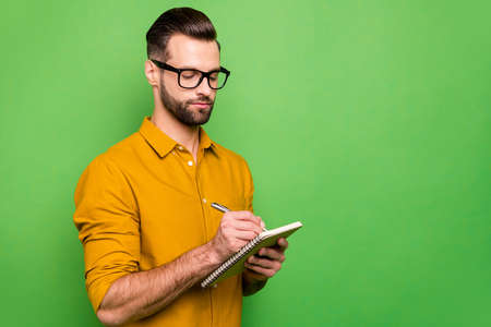 Close-up portrait of his he nice attractive focused intelligent bearded guy in casual formal shirt office manager writing schedule isolated on bright vivid shine vibrant green color background