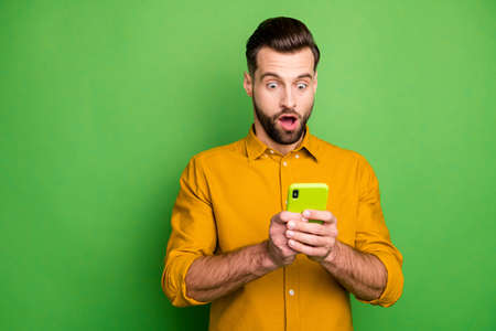 Portrait of his he nice attractive amazed stunned bearded guy in formal shirt using 5g app reading fake news isolated on bright vivid shine vibrant green color background Reklamní fotografie