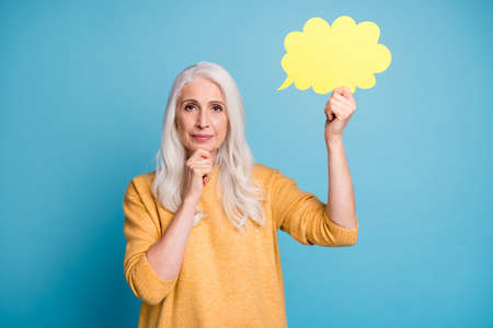 Close-up portrait of her she nice attractive lovely charming minded grey-haired woman holding idea paper card thinking touching chin isolated over bright vivid shine vibrant blue color background