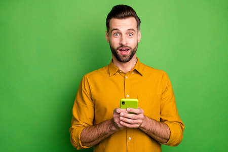 Close-up portrait of his he nice attractive cheerful amazed bearded guy in formal shirt holding in hands cell great news isolated on bright vivid shine vibrant green color background