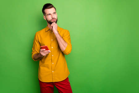 Portrait of his he nice attractive serious minded guy in formal shirt holding in hand cell thinking creating smm idea isolated on bright vivid shine vibrant green color background
