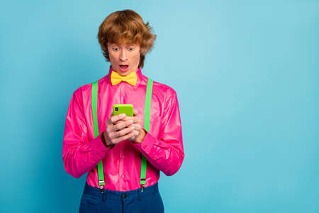 Portrait of astonished guy use smartphone read social network information impressed scream wow omg wear stylish modern pants trousers isolated over blue color background