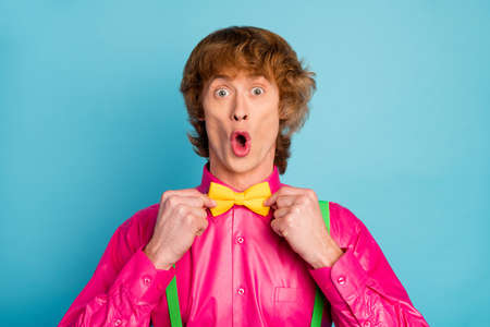 Portrait of astonished funky man stare mirror prepare for dress code prom party adjust bow tie impressed his look shout wear stylish clothes isolated over blue color background