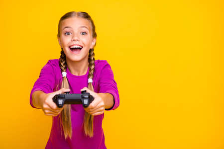 Close-up portrait of her she nice attractive lovely excited cheerful cheery girl playing video game having fun sign isolated over bright vivid shine vibrant yellow color background Standard-Bild - 140454696