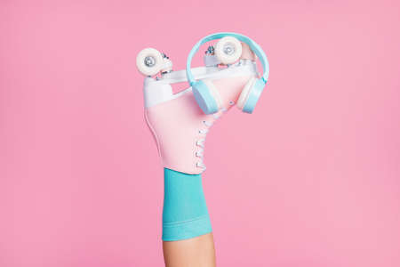 Cropped view of one nice attractive lovely single leg wearing blue sock skates ear phones modern fashionable radio hit isolated over pink pastel color background