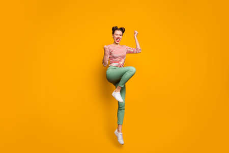 Full length photo of pretty attractive lady traveler jumping high up raise fists scream astonished wear striped red white shirt green trousers sneakers isolated yellow color background