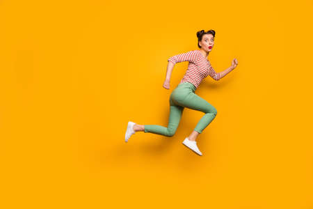 Wow! Full body side photo of pretty lady open mouth jump high rush sale shopping center wear red white shirt green pants footwear isolated bright yellow background