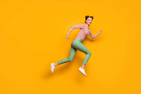 Full length photo of pretty lady jumping high rushing low prices sales shopping center wear red white pullover shirt green pants footwear isolated bright yellow background Stok Fotoğraf