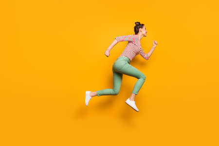 Full size profile photo of pretty crazy lady jumping high rushing low prices sales addicted shopper wear red white pullover shirt green pants footwear isolated bright yellow background