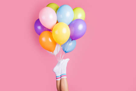 Cropped view of nice attractive legs wearing white casual socks holding bunch air balls fest gift present surprise girlfriend, isolated over pink pastel color background Banco de Imagens