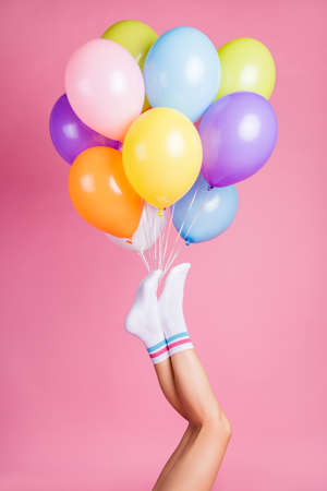 Vertical cropped view of nice attractive lovely long feminine legs wearing white casual soft socks holding bunch air balls fest, isolated over pink pastel color background
