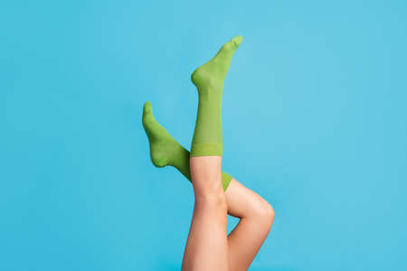 Cropped profile side view of nice attractive long legs wearing cosy comfortable mint green brandy socks posing, isolated over bright vivid shine vibrant blue color background Banco de Imagens