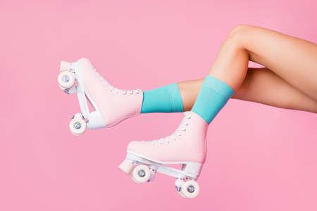 Vista lateral de perfil recortado de piernas largas femeninas encantadoras atractivas agradables con calcetines azules patines patinando posando divirtiéndose en el aire aislado sobre fondo de color rosa pastel