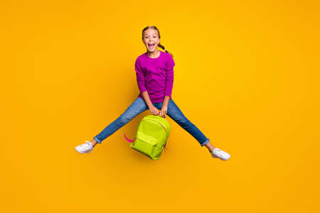Full length body size view of her she nice attractive lovely excited cheerful cheery girl jumping carrying bag having fun isolated on bright vivid shine vibrant yellow color background