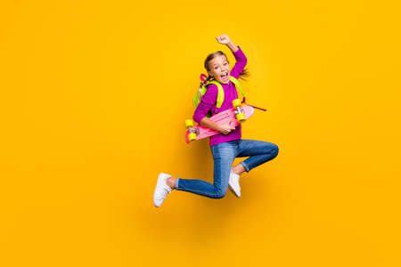 Full length body size view of her she nice attractive lovely pretty cheerful cheery girl jumping carrying longboard rejoicing isolated on bright vivid shine vibrant yellow color background Stok Fotoğraf