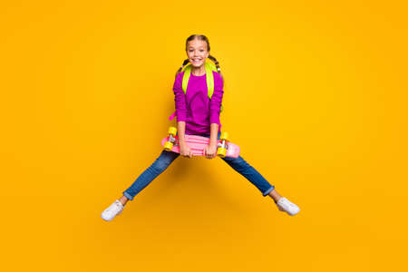 Full length body size view of her she nice attractive glad cheerful cheery girl jumping carrying longboard pass exam test isolated on bright vivid shine vibrant yellow color background