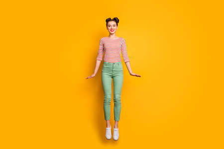Full length photo of attractive pretty lady jumping high up rejoicing traveler abroad wear red white pullover shirt green pants footwear isolated bright yellow background