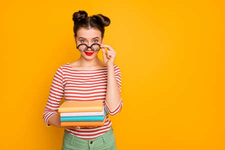 Photo of student nerd lady hold many books look tricky taking off funny freak glasses wear striped red white shirt green pants isolated bright yellow color background 版權商用圖片
