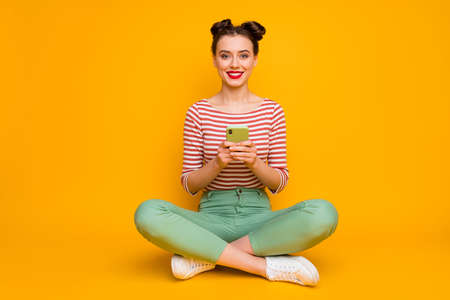 Full size photo of attractive lady sit floor legs crossed hold telephone check new followers subscribers wear striped red white shirt green pants shoes isolated yellow color background 版權商用圖片