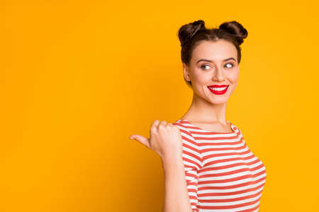 Closeup photo of pretty funny lady shine glossy lipstick direct thumb finger empty space advising novelty product wear striped red white shirt isolated bright yellow color background 版權商用圖片