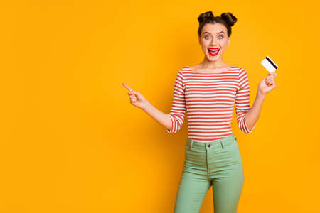 Photo of pretty excited funny lady hold credit card wireless online money direct finger empty space wear striped red white shirt green pants isolated bright yellow color background
