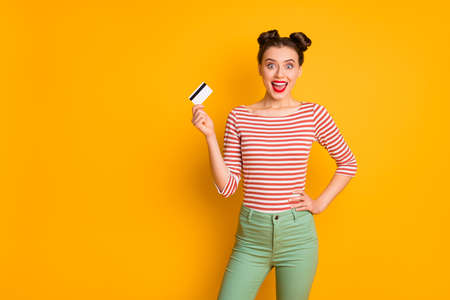 Photo of pretty excited funny lady open mouth holding credit card wireless online money wear striped red white shirt green pants isolated bright yellow color background