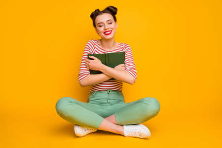 Full length photo of pretty lady sit floor legs crossed hold book close to chest dreamer eyes closed wear striped red white shirt green pants footwear isolated yellow color background 版權商用圖片