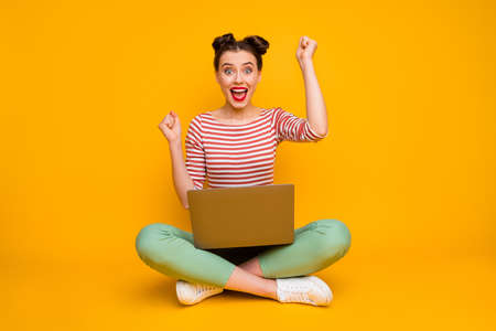 Wow Full size photo of pretty shocked lady sit floor hold notebook read good information raise fists wear striped red white shirt green pants shoes isolated yellow color background 版權商用圖片