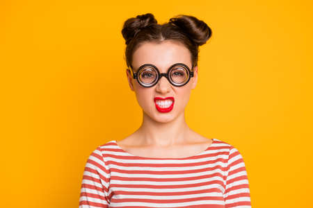 Closeup photo of pretty crazy lady student grimacing grinning showing teeth wear round circle geek specs striped red white shirt isolated bright yellow color background