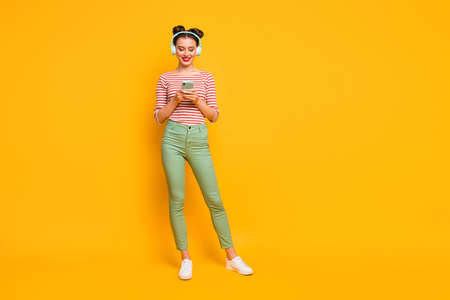 Full length photo of pretty lady use telephone turn on favorite melody modern technology earphones wear red white shirt green pants footwear isolated bright yellow color background 版權商用圖片