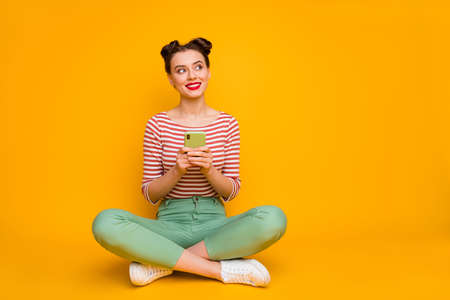 Full length photo of attractive lady sit floor hold telephone hands look up empty space think new post idea wear striped red white shirt green pants shoes isolated yellow color background 版權商用圖片