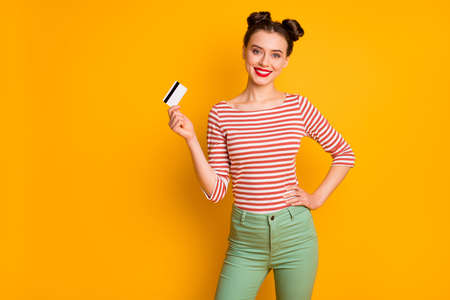 Portrait of her she nice-looking attractive lovely confident cheerful cheery girl holding in hands new unlimited bank card isolated over bright vivid shine vibrant yellow color background 版權商用圖片