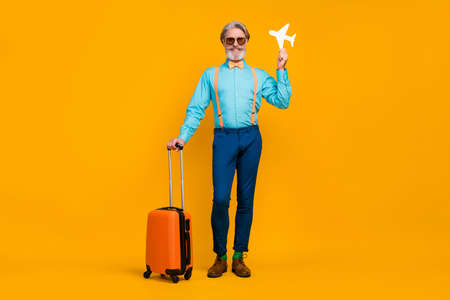 Full length photo of cool grandpa hold paper plane recommend flight traveling rolling suitcase wear blue shirt suspenders bow tie pants boots socks isolated yellow color background Zdjęcie Seryjne - 140588375