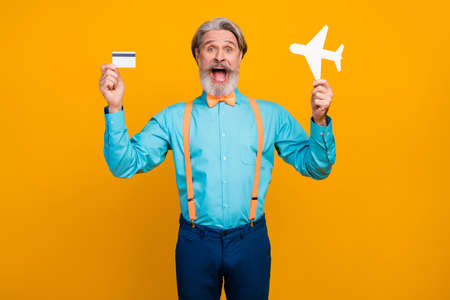 Photo of cool grandpa hold paper air plane recommend online buying tickets use plastic credit card wear blue shirt suspenders bow tie pants isolated yellow color background Zdjęcie Seryjne