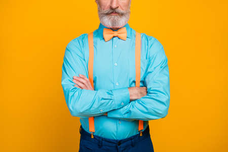 Cropped photo of handsome cool clothes grandpa hands crossed not smiling perfect groomed mustache beard wear blue shirt, suspenders bow tie pants isolated yellow color background