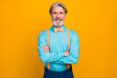 Photo of handsome cool clothes look grandpa good mood hands crossed toothy smiling wear blue shirt suspenders bow tie trousers isolated, yellow color background