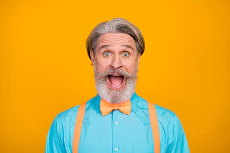 Closeup photo of funny stylish clothes grandpa positive facial expression open mouth see sale shopping advert wear blue shirt suspenders bow tie, isolated yellow color background
