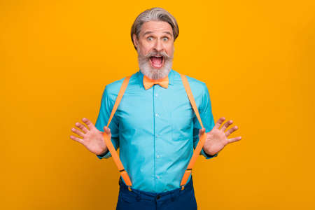 Photo of handsome cool clothes grandpa amazed good mood ready for party chilling celebrating wear blue shirt suspenders bow tie, isolated yellow color background