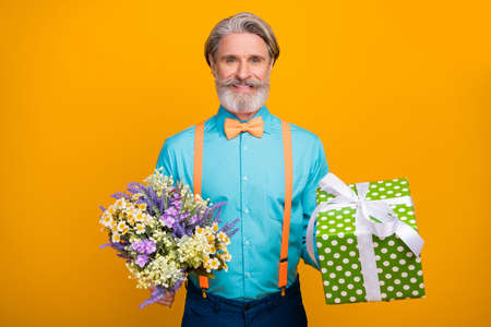 Photo of handsome trendy grey haired grandpa hold fresh bunch wildflowers big gift box girlfriend wife birthday wear blue shirt suspenders bow tie, isolated yellow color background Stockfoto